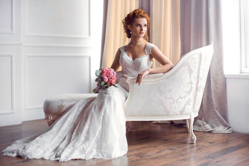Brud i härligt klänningsammanträde som inomhus vilar på soffan royaltyfria foton