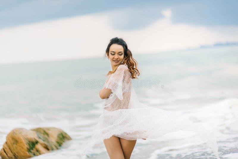 Brud i hennes underkläder och en dressingkappa arkivbilder