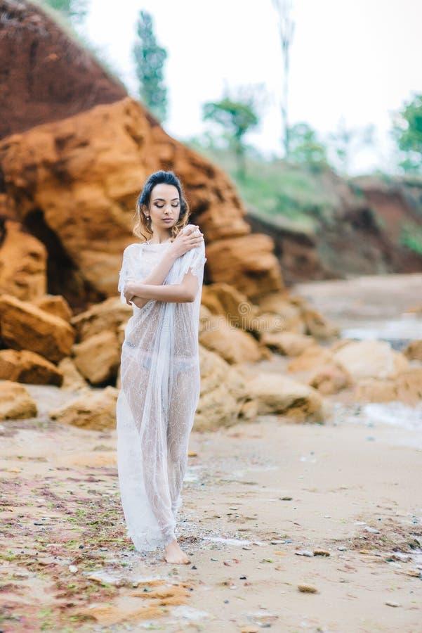 Brud i hennes underkläder och en dressingkappa arkivfoto