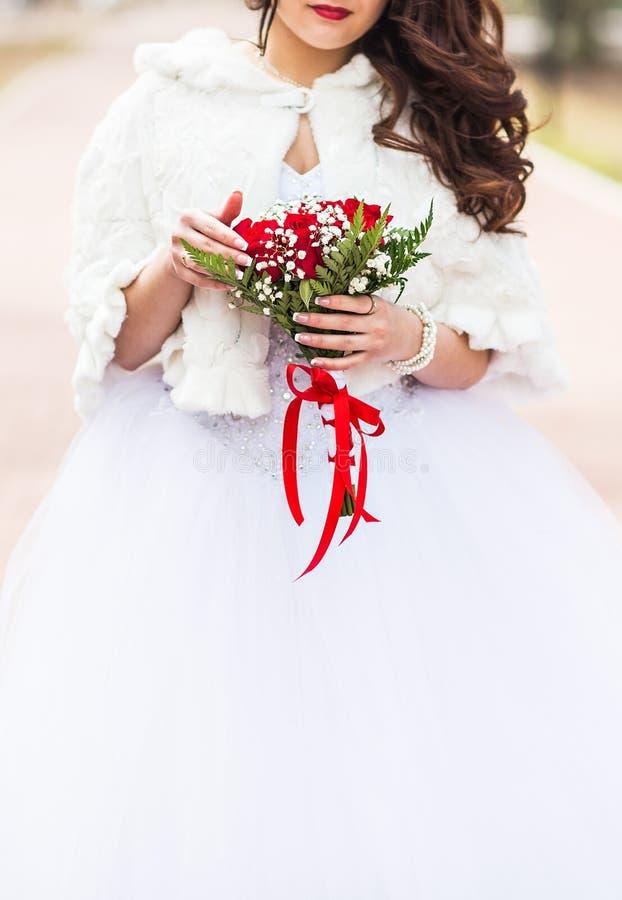 Brud med blommabuketten i vinter royaltyfri bild