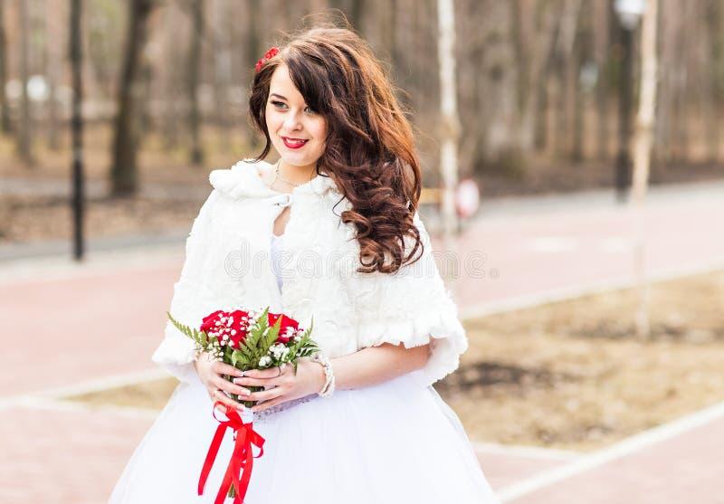 Brud med blommabuketten i vinter fotografering för bildbyråer