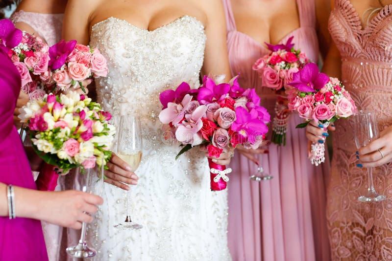 Brud med brudtärnor som rymmer den härliga blommabuketten arkivfoton