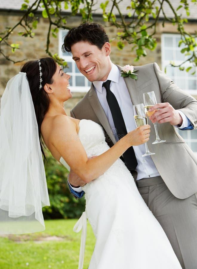Brud och brudgum Drinking Champagne At Wedding arkivfoto