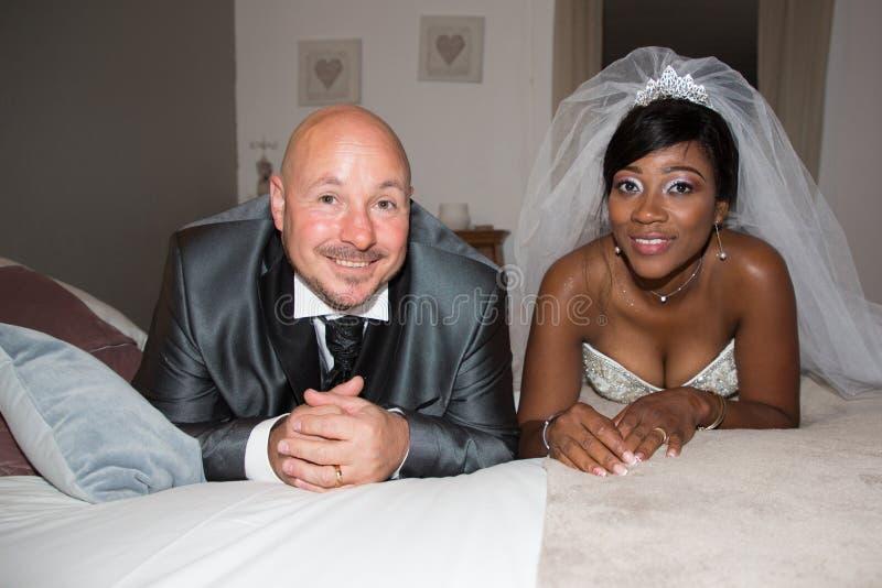 brud och brudgum för mellan skilda raser par som afrikansk caucasian amerikansk hemma ligger på säng i bröllop royaltyfri fotografi
