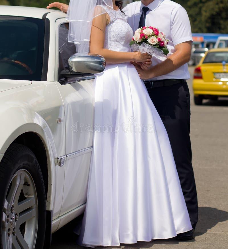 Brud och brudgum framme av bröllopbilen arkivbild