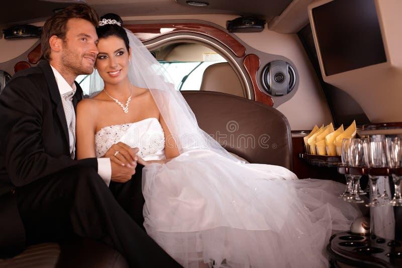 Brud och brudgum, i att le för limo royaltyfria foton