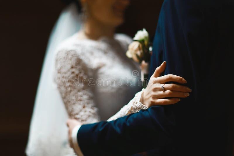 Brud och brudgum i en snöra åtklänning och en dräkt med en fjäril med en budoner med beigea och vita blommor, begrepp av förälske royaltyfri bild