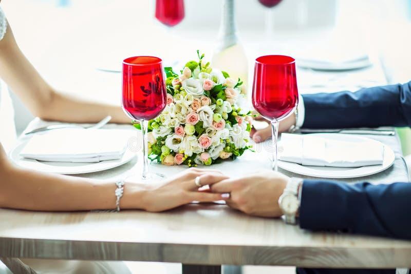 Brud och brudgum i ett dräktsammanträde på den tjänade som tabellen som tjänas som tabellen för bruden och brudgummen, bröllopdek royaltyfri bild