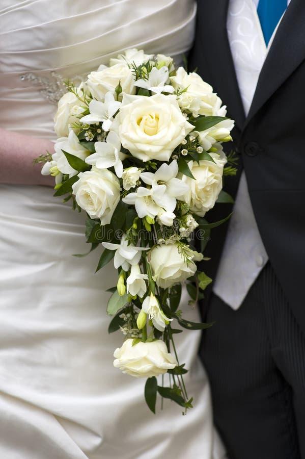 Brud och brudgum med bröllopbuketten royaltyfria foton