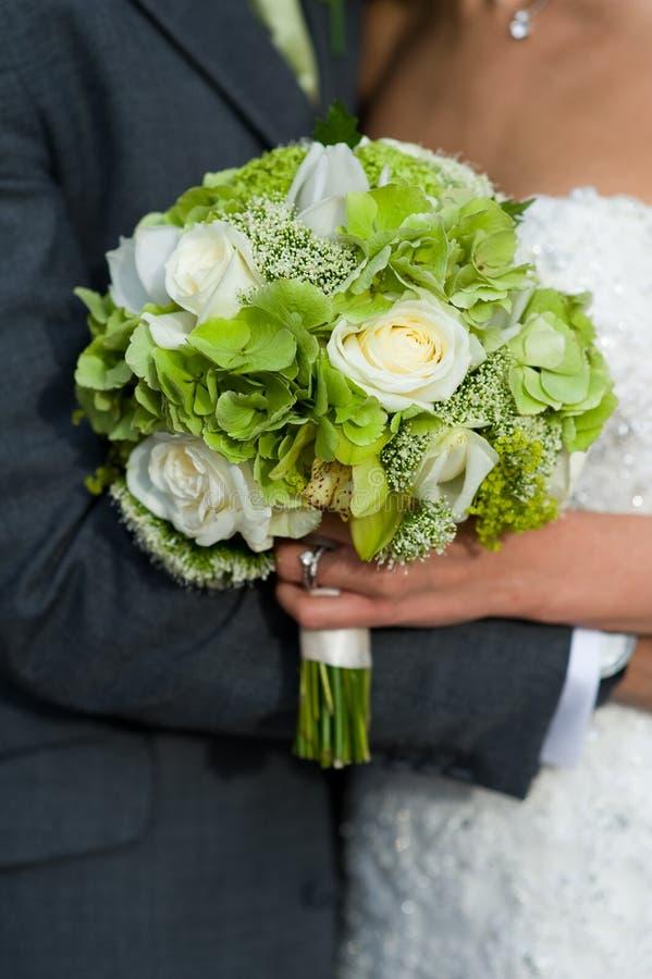 Brud och brudgum med bröllopbuketten fotografering för bildbyråer
