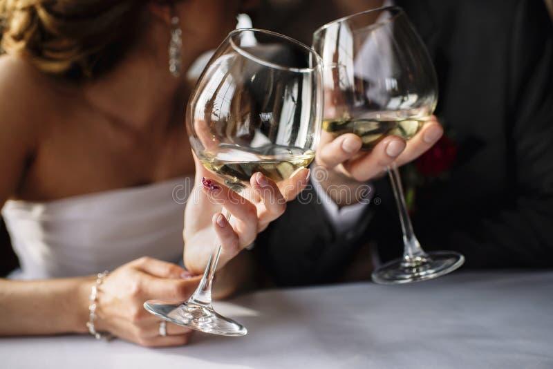 brud och brudgum med exponeringsglas av vin i händer royaltyfria foton