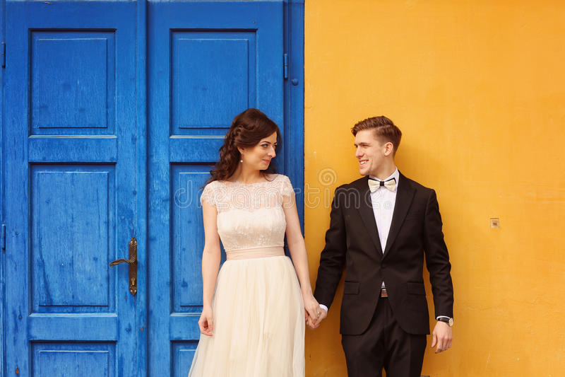 Brud och brudgum mot gul vägg- och blåttdörr royaltyfria foton