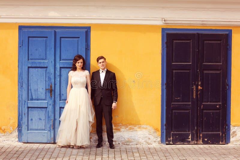 Brud och brudgum mot gul vägg- och blåttdörr royaltyfri bild