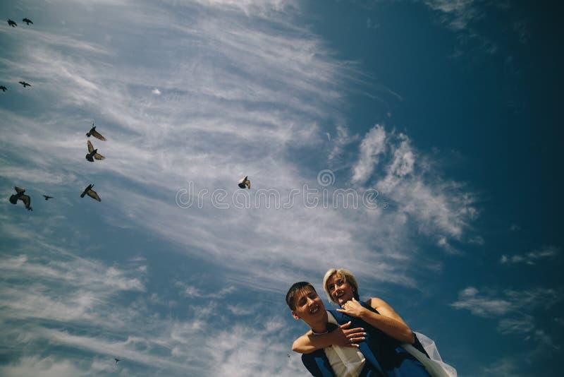 brud och brudgum på bakgrunden av himmel arkivfoto