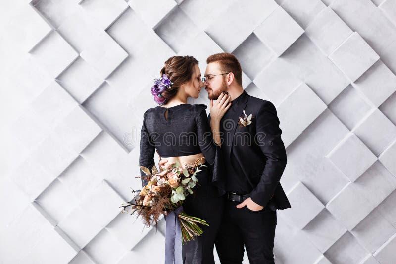Brud och brudgum på bakgrundsgrå färgfyrkanterna i studio Tillbaka sikt av bruden, fokus på brudgum Gifta sig lovestory begrepp royaltyfria foton