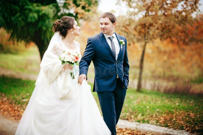 Brud och brudgum på bröllopdagen som utomhus går royaltyfri foto