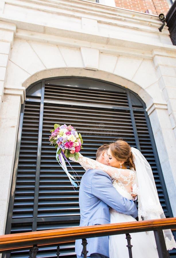 Brud och brudgum på bröllopdagen som utomhus går Lyckligt omfamna för nygifta personer älska för par royaltyfri fotografi