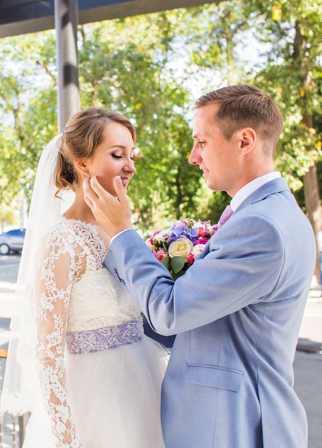 Brud och brudgum på bröllopdagen som utomhus går Lyckligt omfamna för nygifta personer älska för par royaltyfria foton