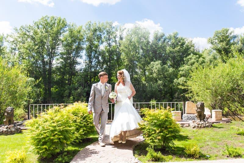 Brud och brudgum på bröllopdagen som utomhus går på vårnaturen Brud- par, lycklig nygift personkvinna och omfamna för man arkivbilder