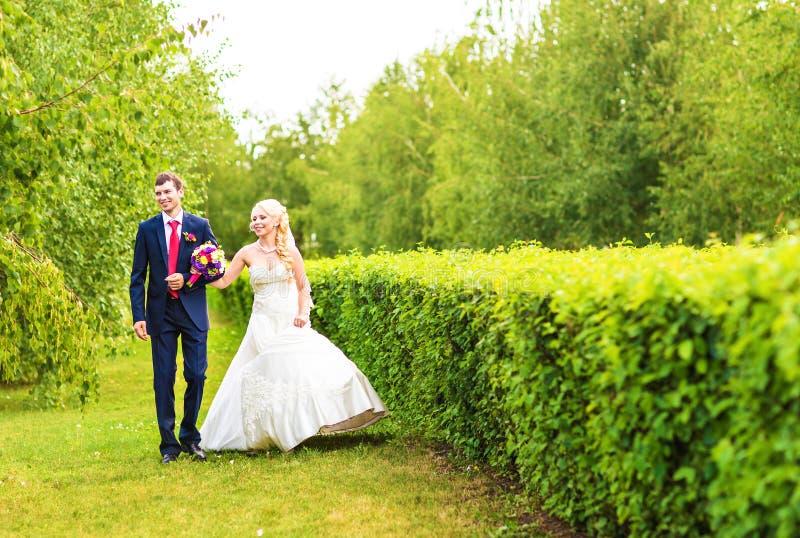 Brud och brudgum på bröllopdagen som utomhus går på vårnaturen Brud- par, lycklig nygift personkvinna och omfamna för man fotografering för bildbyråer