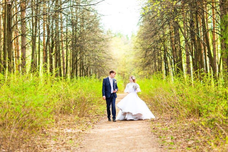 Brud och brudgum på bröllopdagen som utomhus går på vårnaturen Brud- par, lycklig nygift personkvinna och omfamna för man royaltyfri foto