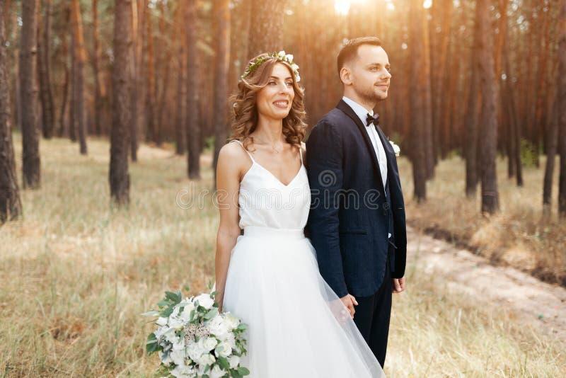 Brud och brudgum på bröllopdagen som utomhus går på sommarnaturen Brud- par, lycklig nygift personkvinna och man som omfamnar i g royaltyfria foton