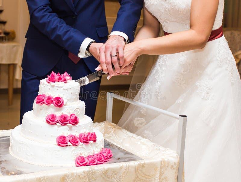 Brud och brudgum på bröllopmottagandet som klipper kakan royaltyfria foton