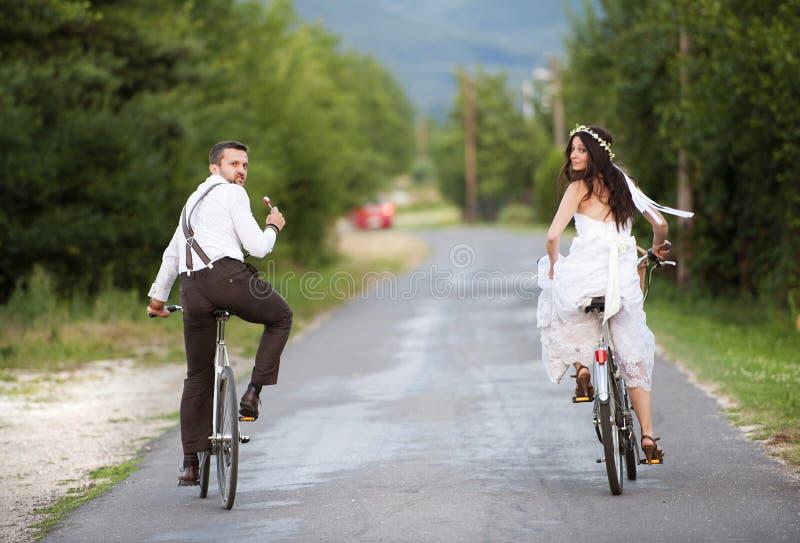 Brud och brudgum på cyklarna royaltyfri fotografi