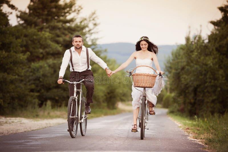Brud och brudgum på cyklarna royaltyfri foto
