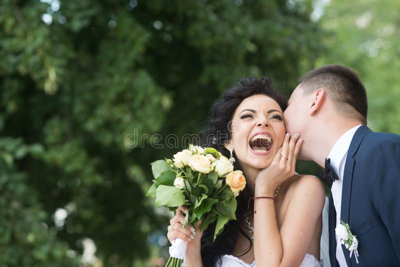 Brud och brudgum på den utomhus- bröllopdagen på vårnaturen Brud- par, lycklig nygift personkvinna och man som omfamnar i gräspla fotografering för bildbyråer