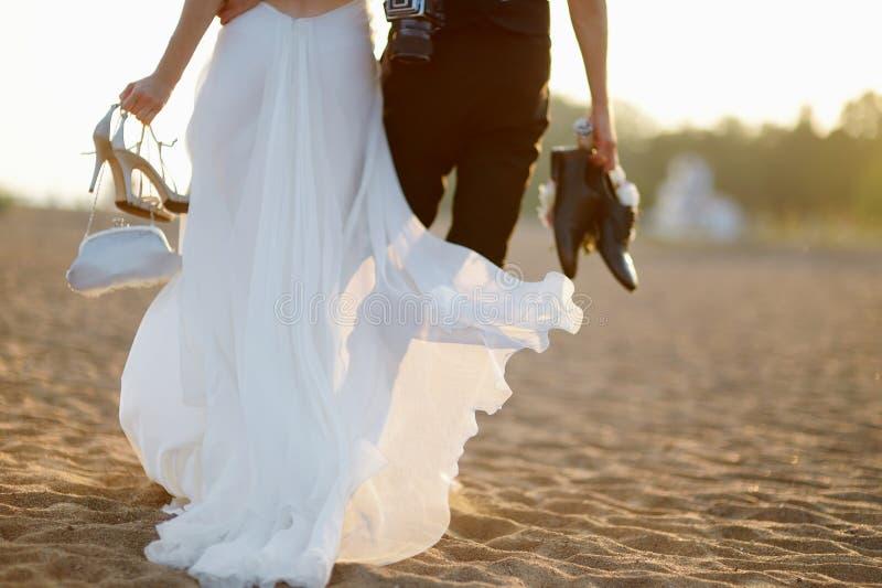 Brud och brudgum på en strand på solnedgången royaltyfri bild