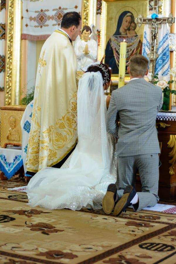 Brud och brudgum på kyrkan under en bröllopceremoni arkivbilder