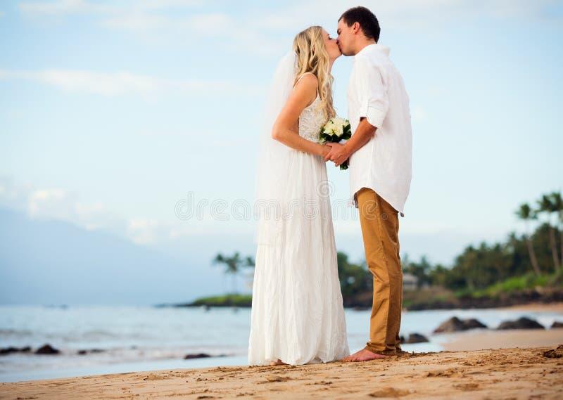 Brud och brudgum på solnedgången på den tropiska stranden royaltyfria foton