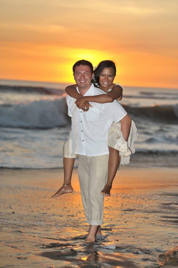 Brud och brudgum som barfota går på stranden royaltyfri fotografi