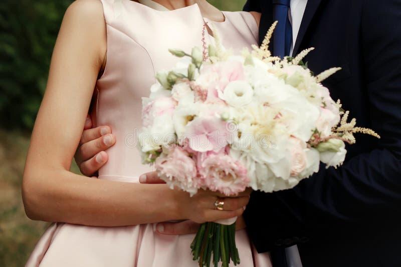 Brud och brudgum som kramar, lyxigt brölloppar med fantastisk bouq royaltyfria foton