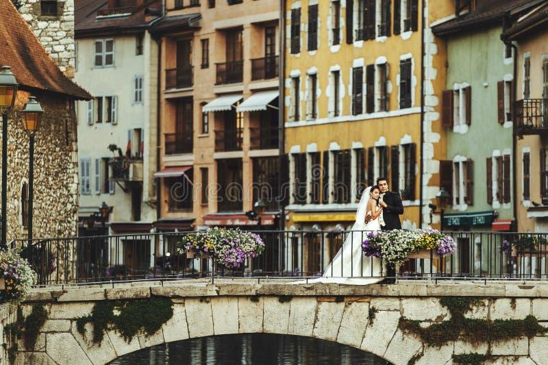 Brud och brudgum som kramar på den gamla romantiska bron över floden och ch arkivfoton