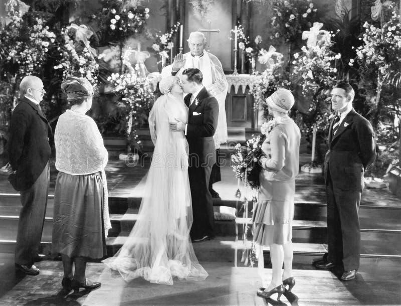 Brud och brudgum som kysser efter bröllopceremonin (alla visade personer inte är längre uppehälle, och inget gods finns Leverantö arkivbilder