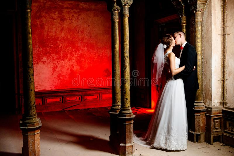 Brud och brudgum som kysser i den gamla slotten arkivfoto