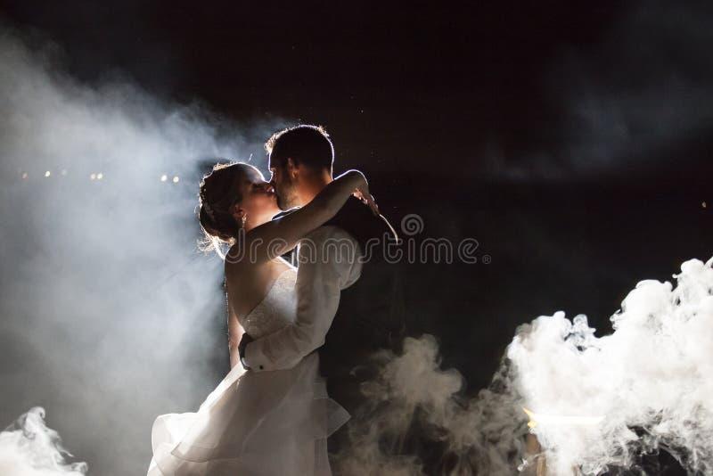 Brud och brudgum som kysser under dimma på natten royaltyfri foto