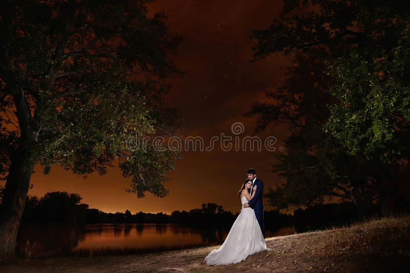 Brud och brudgum som omfamnar vid sjön under stjärnorna royaltyfria foton