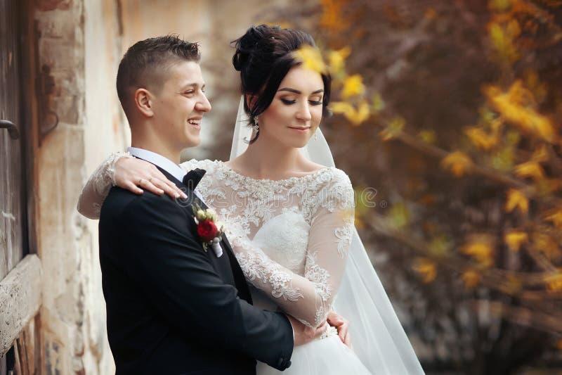 Brud och brudgum som poserar och kramar nära gammal byggnadsväggcloseu royaltyfria bilder