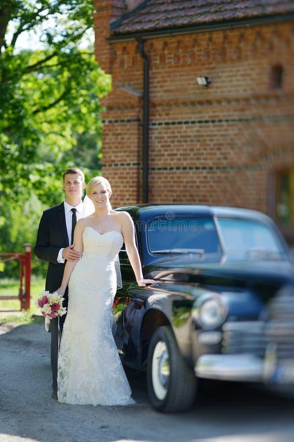 Brud och brudgum som poserar vid en bil arkivbild