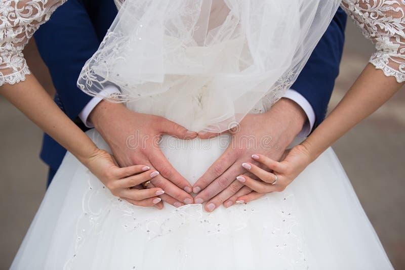 Brud och brudgum som rymmer deras händer i en hjärtaform arkivbild