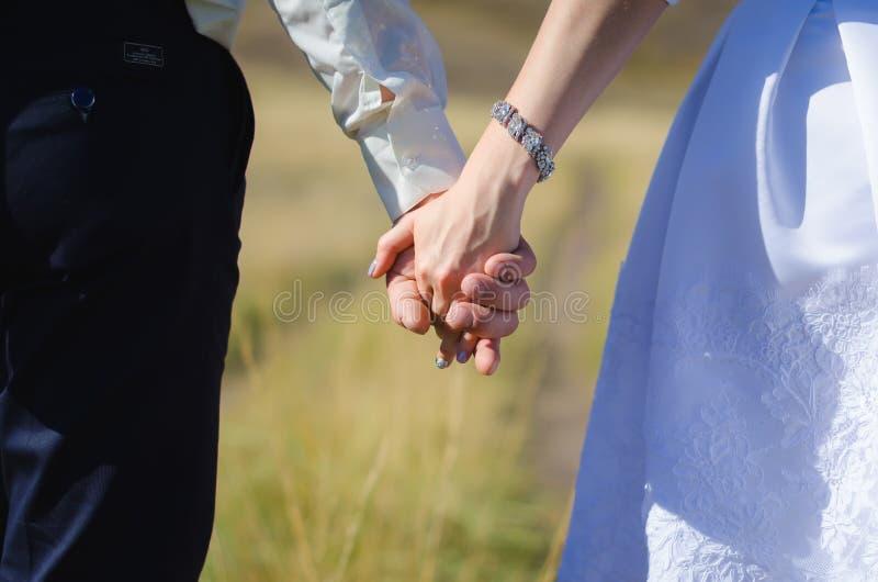 Brud och brudgum som rymmer sig händer arkivfoto