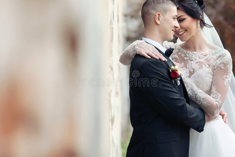 Brud och brudgum som skrattar och kramar nära gamla byggnadsväggclos arkivbilder