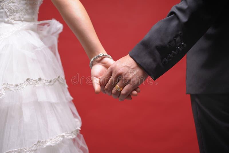 Brud- och brudgumanseende samman med hjärta arkivfoton
