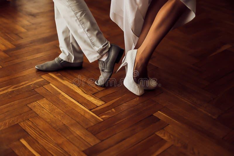 Brud- och brudgumbröllopskor Härliga vita skor på höga häl Kvinnaben royaltyfri fotografi