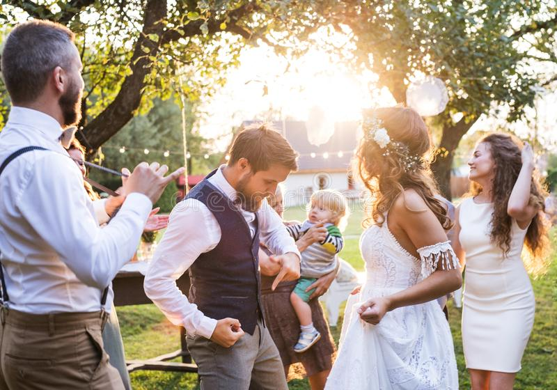 Brud- och brudgumdans på bröllopmottagandet utanför i trädgården royaltyfri bild