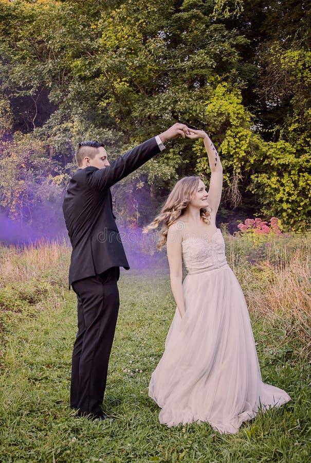 Brud- och brudgumdansen i skog med lilor röker arkivfoton