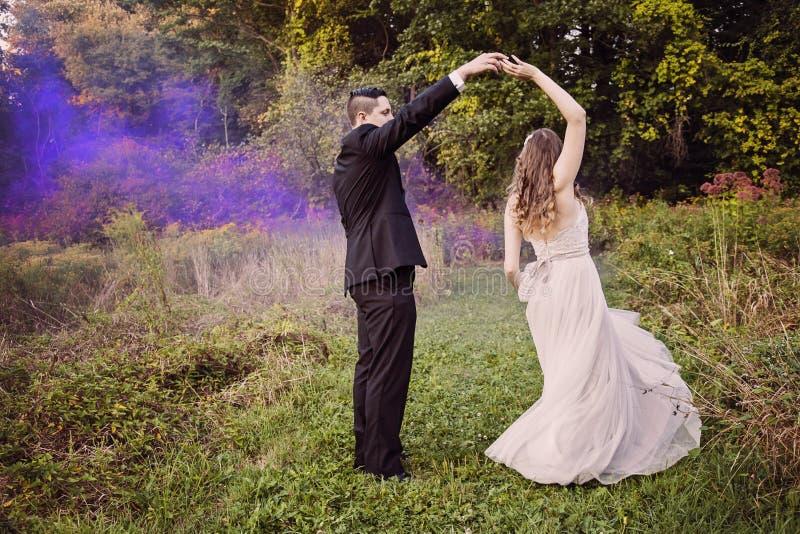 Brud- och brudgumdansen i skog med lilor röker fotografering för bildbyråer